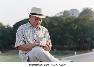 Asian old man sitting and relaxing in public park.