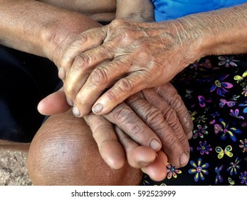 Asian old man touches and holds hand old woman,Growing Old Together