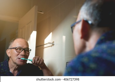 Asian old man wear glasses is brushing Teeth and looking through the mirror in the bathroom.