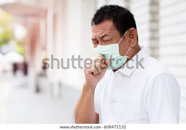 A asian Old man wearing a face mask in the city coughing