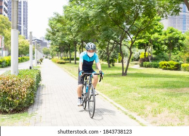 Asian old man wearing helmet and face mask is riding a bicycle in the park - enjoying sport or hobby living healthy