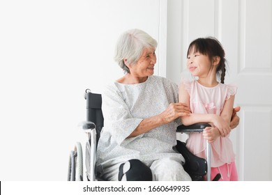 Asian old patient woman on wheelchair sickness feeling happy and smile with young little girl in hospital