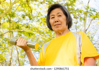 asian old woman concentrate on exercising with dumbbell.