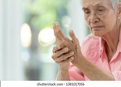 Asian old woman is massaging her own hand,Elderly woman suffering from pain in hand,arthritis,beriberi