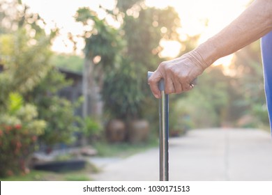 Asian old woman standing with his hands on a walking stick,Hand of old woman holding a staff cane