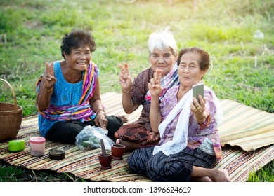 Asian old woman using mobile phone selfie