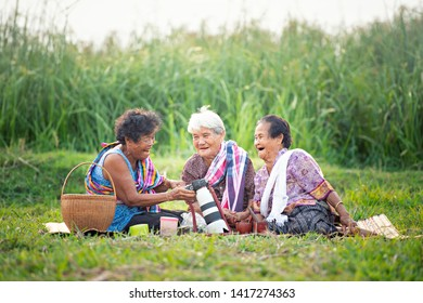 Asian old women viewing photos on modern camera in park with happily.