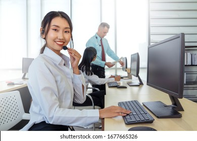 Asian operator woman working in a call center, Female technical support answering customer questions, Customer service using a headset, Concept of Business telemarketing and communication support
