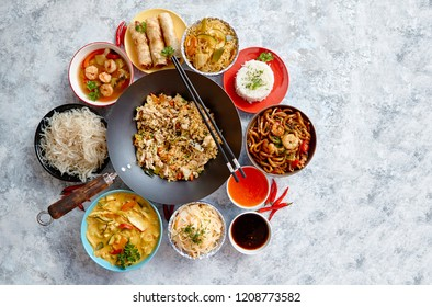 Asian oriental food composition in colorful dishware, served on stone, top view. Chinese, vietnamese, thai cuisine set. With copy space