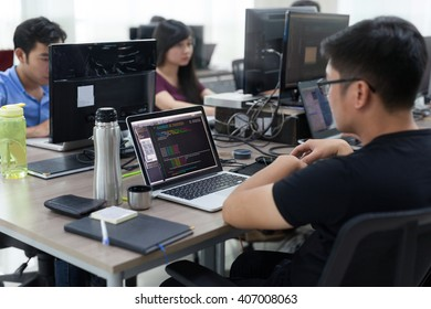 Asian Outsource Developer Team Sitting At Desk Working Laptop Computer Mobile Application Software Real Office