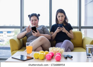 asian Overweight woman with friend play mobile phone and enjoy eating food and popcorn on sofa at home