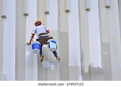 An Asian painter hanging to paint with high building