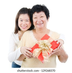 Asian parent and adult offspring holding a gift box smiling, isolated on white background.