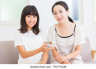 asian parent and daughter with a smartphone
