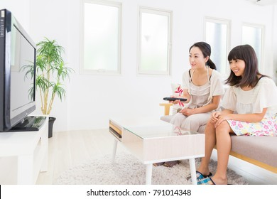 asian parent and daughter watching TV in living room
