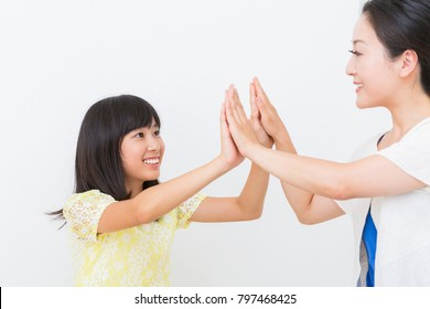 asian parent and daughter who high-five