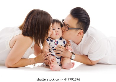 Asian parent kiss their baby girl