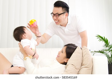 Asian parent playing with their baby at home