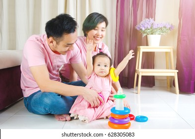Asian parent playing with their baby girl at home
