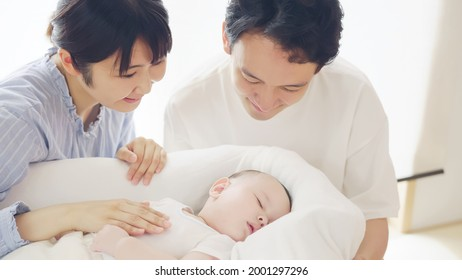 Asian parents and baby in the room. Child rearing concept.