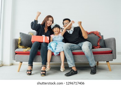 Asian parents and children to play on the sofa.Asian happy family and daughter laughing on sofa