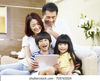 asian parents and children sitting on couch having fun with digital tablet.