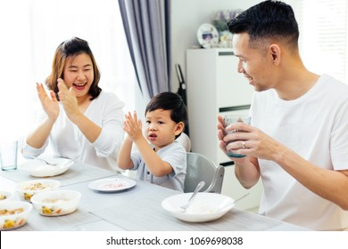 Asian parents clapping hands and giving compliment as their child does good job while having meal together at home