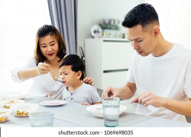 Asian parents feeding their child and the whole family having meal together at home