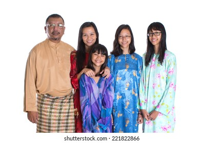 Asian parents with teen daughters in traditional attire over white background