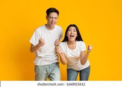 Asian partners rejoicing success, clenching fists and exclaiming with triumph, standing next to each other on yellow background