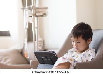 Asian patient boy with saline intravenous (iv) on hospital sofa, sick boy using digital tablet