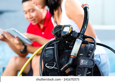 Asian people, divingmaster and student at the diver Course on holiday with wetsuit and tablet computer