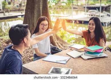 Asian people doing high five for start up new project. Business of youth concept. Successful and Teamwork of teen theme. Books and tablet and lecture paper elements
