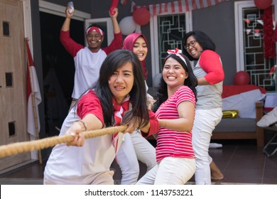 asian people doing tug of war competition on indonesia independence day
