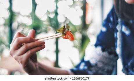 Asian people eating sashimi set in Asian restaurant. Hirame sashimi,salmon sashimi and tuna sashimi dish.