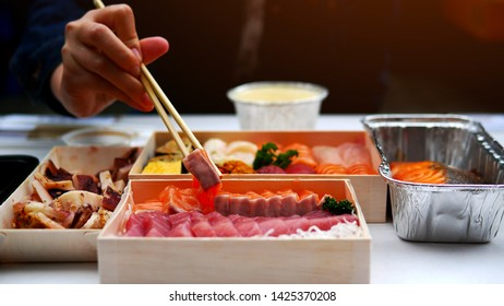 Asian people eating sashimi set in Asian restaurant. Hirame sashimi,salmon sashimi, Sea urchin Uni sashimi and tuna sashimi dish.