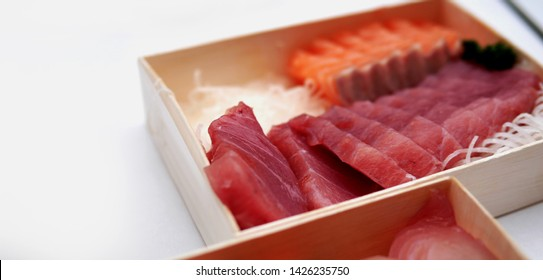 Asian people eating sashimi set in Asian restaurant. Hirame sashimi,salmon sashimi and tuna sashimi dish.