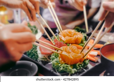 Asian people eating sashimi set in Asian restaurant
