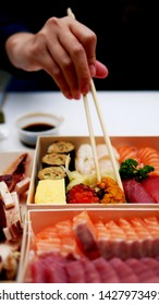 Asian people eating sushi and sashimi set in Asian restaurant. Hirame sashimi,salmon sashimi, Sea urchin Uni sashimi and tuna sashimi dish. People using chopsticks are clamping sushi, eggs, sea urchin