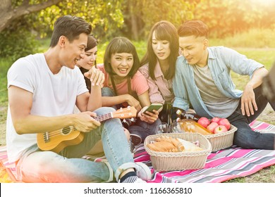 Asian people look something at cellphone with his friends in the park
