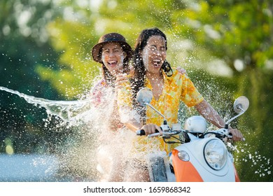 Asian people play songkran festival in the summer april They ride motorcycles. Then hit the water