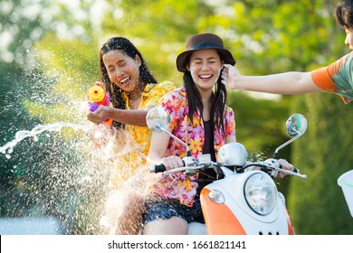 Asian people play songkran festival in the summer april They ride motorcycles. Then hit the powder