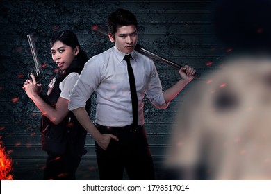 Asian people in police vest standing with a baseball bat and gun with zombies on the background