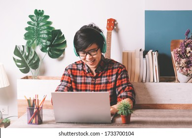 Asian People Short Hair Working on Laptop Computer and Wearing Stereo Headset to Listening Music While Working from Home at Living Room , Remote Work, Live Streaming , Relaxing Concept