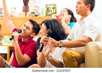 Asian people singing at karaoke party and having fun