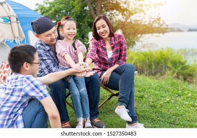 asian people and sunlight ,asian family travel and camping in forest, they sitting and feel happy at lakeside , they use hand touch hand together, hand in hand, family activity, adventure and travel