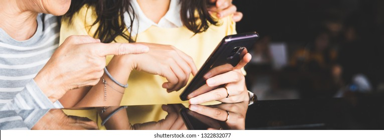 Asian people using smartphone together, close-up at hands, banner size with copy space. Modern technology lifestyle, advanced mobile communication, or internet network connection concept
