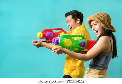 Asian people are using water guns play in the Songkran festival. Studio concept