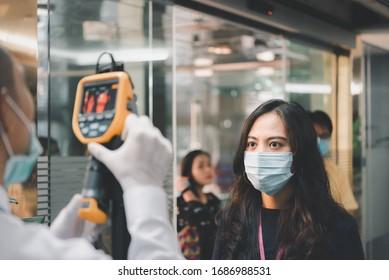 Asiatische Menschen, die auf eine Körpertemperaturkontrolle warten, bevor sie durch Thermoscan oder Infrarot-Wärmekamera Zugang zu Gebäuden gegen Epidemie-Grippe-Covid19 oder Corona-Virus von Wan im Amt haben