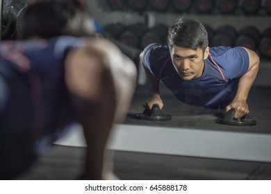 Asian people work out by push up the floor in  modern gym.